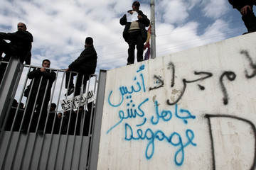 Employees of Tunisia's Transport Company (TTC) stand near graffiti during a strike at their bus depot in Tunis