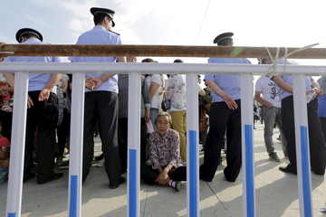 A 76-year-old local villager sit outside the fence as people wait for IOC's announcement of the winner city for the 2022 winter Olympics bid in Chongli county of Zhangjiakou