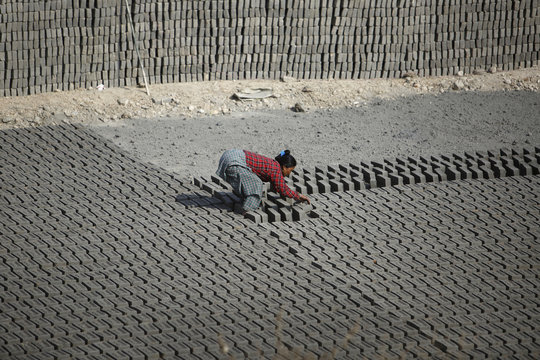 A woman flips bricks laid out to dry out in the sun before baking them at a brick factory in Lalitpur