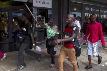 South African men run from police as rioting and looting was quelled during anti-foreigner violence in Durban