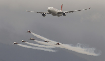 Switzerland's Air Force national flight team Patrouille Suisse  performs in their Northrop F-5E Tiger II aircrafts beside an Airbus A330-300 jet of Swiss airline during the Flugmeeting Emmen 2010 in town of Emmen