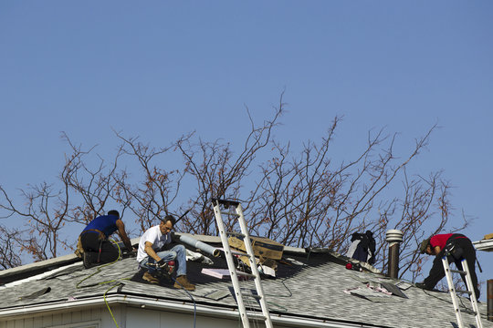 Roofers work to repair damage done to a home by Hurricane Sandy in the Annadale neighborhood of Staten Island, New York