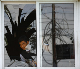 A man looks out from a broken window after a bomb blast at Basundhara in Kathmandu