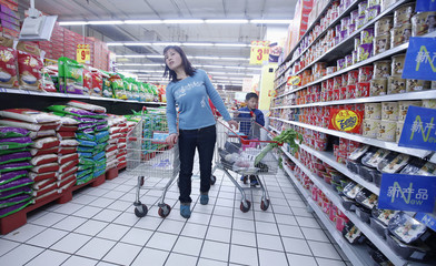 A woman looks for goods at a supermarket in Beijing