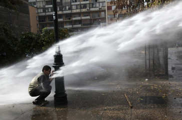 A student tries to take cover from a police water cannon being deployed during a rally in downtown Santiago