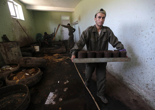 Afghan men work to make briquettes at the basement of NGO, the Kabul Orthopedic Organization (KOO) in Kabul
