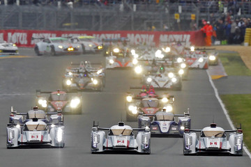 The Audi R18 E-Tron Quattro drivers Lotterer of Germany, Britain McNish and Di Grassi of Brazil drive just ahead of the Toyota TS030 Hybrid cars during the Le Mans 24-hour sportscar race in Le Mans