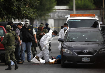 Members of a forensic team prepare to remove the slain body of a man after a drive-by shooting in the municipality of Apodaca