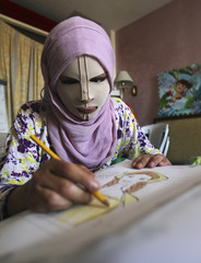 An Iraqi refugee girl, who was injured during the violence in her country, wears a face mask as she colours a drawing during a psychological therapy session in Amman