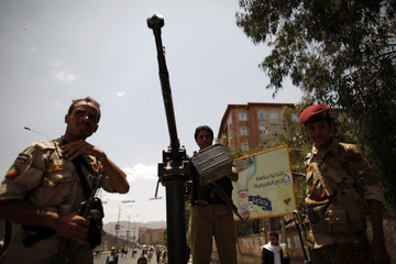 Army soldiers secure a road where protesters rallied to demand that Yemen's former President Ali Abdullah Saleh be put on trial in Sanaa