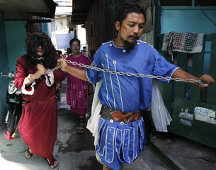 Man portraying Jesus Christ walks as he is pulled on a chain by another portraying a Roman soldier ahead of Good Friday in Mandaluyong city, metro Manila