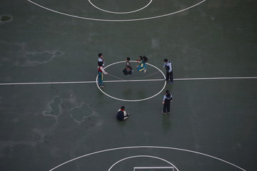Students skipping in the basketball court during a hazy day in Shanghai