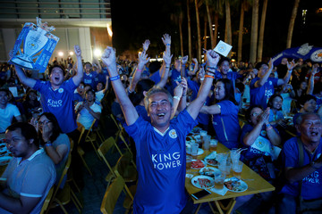 Leicester City fans celebrate after their team scores against Manchester United while watching the game on a big screen in Bangkok
