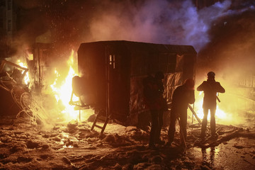 Pro-European protesters stand near vehicles burnt after clashes with Ukrainian riot police in Kiev