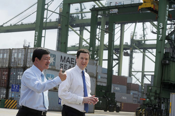 British Chancellor of the Exchequer Osborne is briefed by Tan, regional CEO of PSA Southeast Asia, during a visit to the Port of Singapore