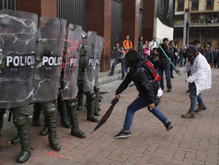 Students react against riot policemen during a protest march in Bogota