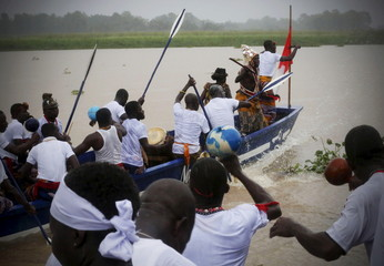 Participants paddle in canoes on the lagoon during the Generation Festival in Moossou