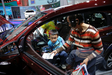 A boy steps out of Venucia T70X SUV at company's booth during the Auto China 2016 auto show in Beijing