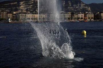 A teenager jumps at the Paquis baths in front of jet d'eau in Geneva