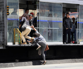 Passengers climb into a Transmilenio system bus station the wrong way in Bogota