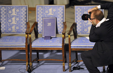 A photographer takes pictures of the empty chairt with diploma and medal of Nobel Peace Prize winner Liu Xiaobo during the Nobel Peace Prize ceremony in Oslo