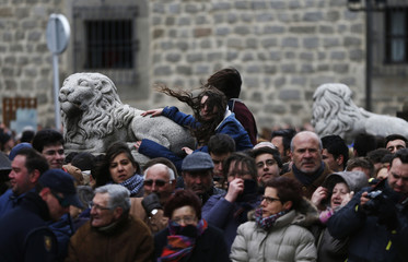 People fight the wind and the cold as they wait to see the hearse carrying former Spanish Prime Minister Adolfo Suarez before his burial at the Cathedral of Avila, northwest of Madrid