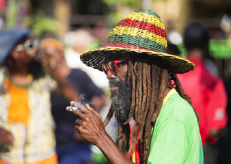 A member of the Rastafarian movement has a spliff at an event in celebration of the 70th anniversary of the birth of late reggae legend Bob Marley in Kingston