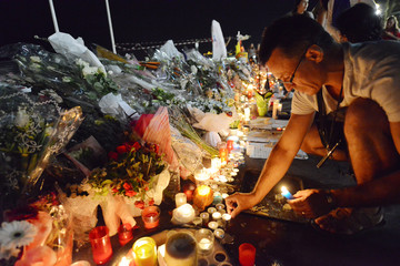 File Photo of a man placing candles near flowers that were left in tribute at makeshift memorials to the victims of the truck attack along the Promenade des Anglais in Nice
