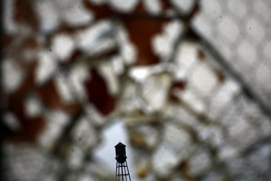 A broken window is seen inside the abandoned and decaying manufacturing plant of Packard Motor Car in Detroit, Michigan