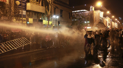 Environment supporters are hit by water jet released by riot police vehicle during a rally against a hydro-power dam project, in Santiago