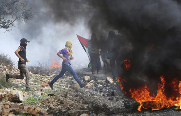 Palestinian protesters run a way from tear gas fired by Israeli soldiers during clashes following a protest against the near-by Jewish settlement of Qadomem, in the West Bank village of Kofr Qadom near Nablus