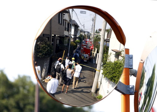 A reflection of onlookers are seen from a traffic mirror along a street in front of the site where a light plane went down in a residential area and burst into flames, in Chofu