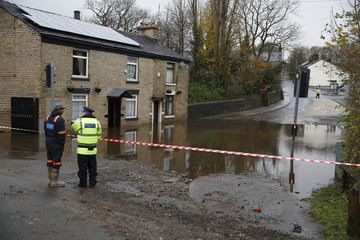 Emergency services personell look at flood water in Stalybridge