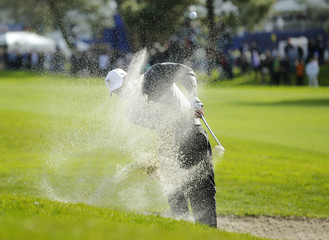 U.S. golfer Woods hits from a fairway trap on the 18th hole during weather delayed third round play at the Farmers Insurance Open in San Diego