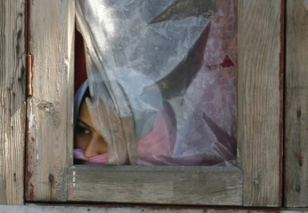 A woman looks out of the window of her house at a rally marking the death anniversary of Muslim cleric Mirwaiz Mohammad Farooq in Srinagar
