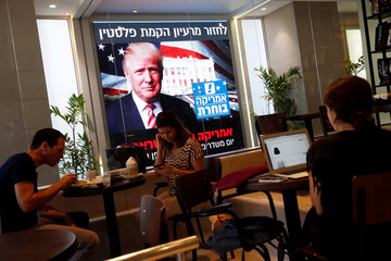 People dine at a coffee shop as an image of newly elected U.S. President Donald Trump is displayed on a monitor in Tel Aviv, Israel