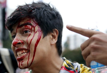 An injured demonstrators shows his head with blood as he attends a protest against fare hikes for city buses in Sao Paulo