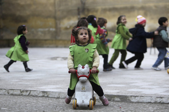 A girl looks up to sky after hearing sound of shelling as she sits on toy pony in playground of Al-Tawheed school in Aleppo