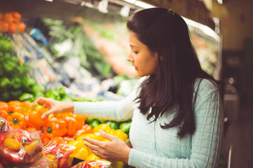 Closeup portrait, young woman in green sweater picking bell peppers with lots of options at grocery store, isolated produce background