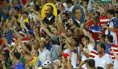 Fans of the U.S. hold up pictures of Martin Luther King Jr and Barak Obama before World Cup Group G soccer match between Ghana and the U.S. at Dunas arena