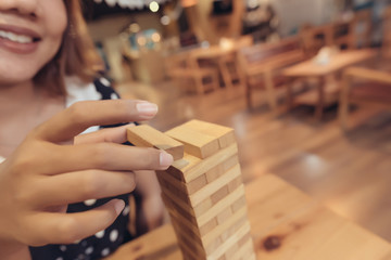Asian woman having fun playing Jenga at the coffee shop in selective focus.