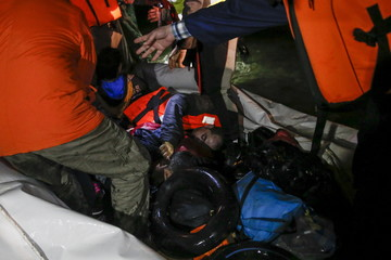 Rescuers stand over an unconscious refugee as refugees and migrants arrive on a dinghy on the shore near the city of Mytilene on the Greek island of Lesbos