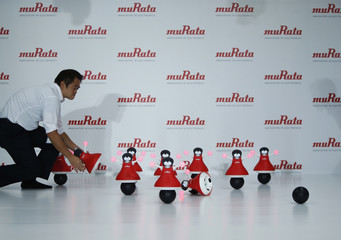 """A staff of Japan's Murata Manufacturing Co. Ltd's picks up some of their latest concept robots, """"the Murata Cheerleaders"""" as they fail to balance at the start of the unveiling event in Tokyo"""