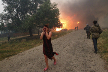 A woman reacts while heavy smoke emits and fire burns in the background due to severe heat, outside the town of Vyksa