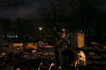 Gabarri reacts as he moves his family's belongings before the demolition of an evangelical church, where they are living in, in Madrid