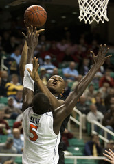 Miami Hurricanes Johnson works to shoot over Virginia Cavaliers Sene during their NCAA men's basketball game at the 2011 ACC Tournament in Greensboro