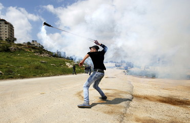 Palestinian protester uses sling to launch tear gas canister, initially fired by Israeli troops, during clashes at a protest marking Land Day, near Israel's Ofer Prison near the West Bank city