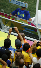 Fans take pictures of Brazil's Neymar sitting on the bench before the start of their 2014 World Cup third-place playoff against the Netherlands at the Brasilia national stadium in Brasilia