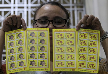 A postal worker holds new postage stamps for 2016, which is the Year of the Monkey according to the Chinese zodiac, inside a post office in Manila