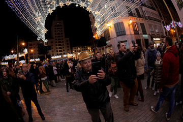 People use mobile phones to take pictures at Marques de Larios street after Christmas lights were turned on to mark the start of the Christmas season in downtown Malaga